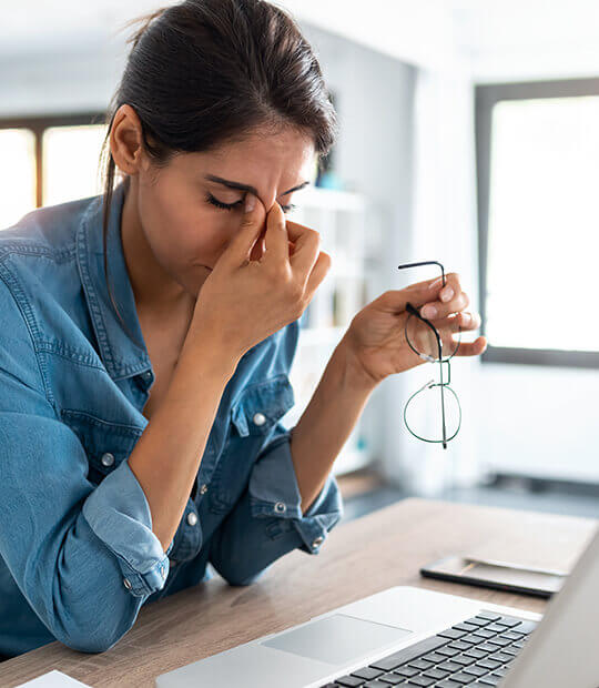 Woman pinching her forehead in frustration.