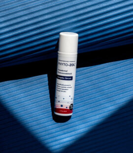 Bottle of Phyto-ZOL on blue yoga mat.